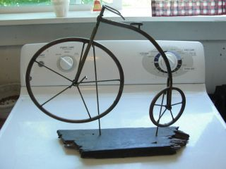 Copper penny farthing, high wheel bicycle on wood stand, decorative