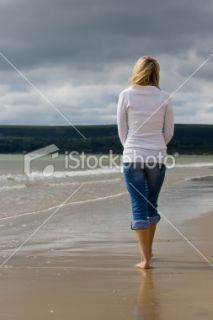 Rear View of Woman On A Beach With Stormy Skies Royalty Free Stock